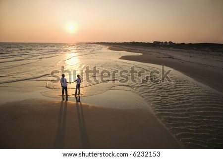 Aerial view of romantic couple standing on beach holding hands on Bald Head Island, North Carolina. - stock photo