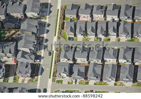 Aerial view of rows of houses and a commuter car heading to work - stock photo