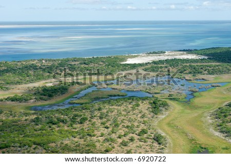 Aerial view of shallow coastal waters and forests of the tropical coast of Mozambique, southern Africa - stock photo