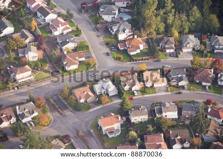 Aerial view of single car driving on a neighborhood road