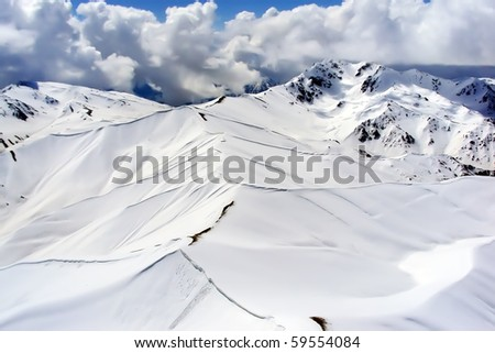 Aerial view of snow-covered mountains under cloudy blue sky - stock photo