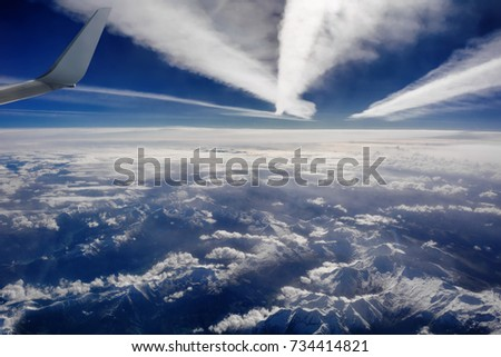 Aerial view of snowy mountains, clouds and plane trails, opposite the sunlight