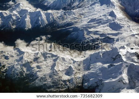 Aerial view of snowy mountains peaks and a winding (serpentine, switchback) road, opposite the sunlight