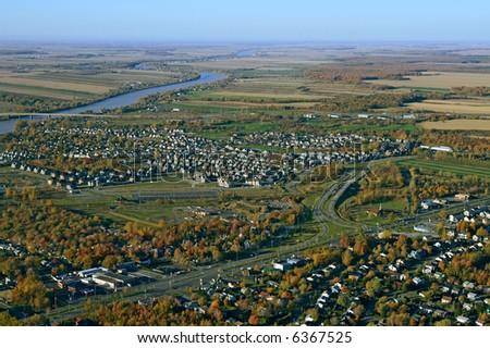 Aerial view of suburban neighborhood near highway in autumn. - stock photo