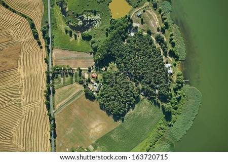 Aerial view of summer field and lake - stock photo