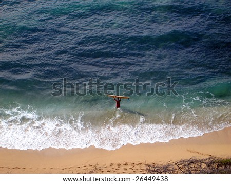 Aerial view of Surfer carrying surfboard into water, Diamond Head Beach, Hawaii - stock photo