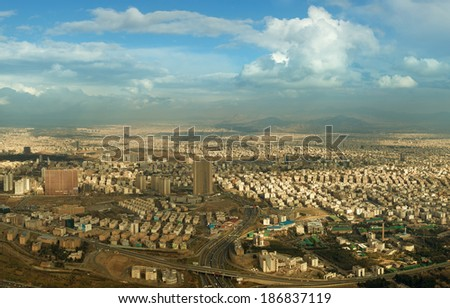 Aerial view of Tehran city against blue sky with fluffy white clouds, shot above Milad Tower. - stock photo