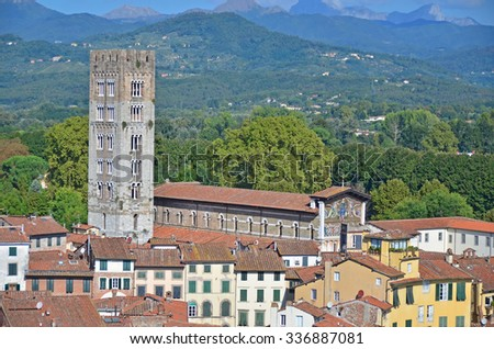 Aerial view of the basilica of St Frediano (an Irish bishop) with it's byzantine style mosaic, in Lucca, Italy. In the background the apennine mountains - stock photo