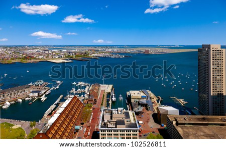 Aerial view of the Boston harbor with Logan international airport in the background.  Sunny with blue sky and white clouds - stock photo