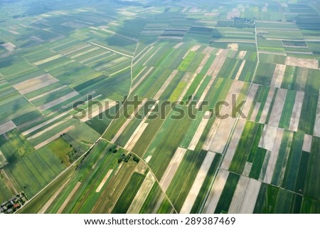 Aerial view of the countryside with village and fields of crops in summer - stock photo
