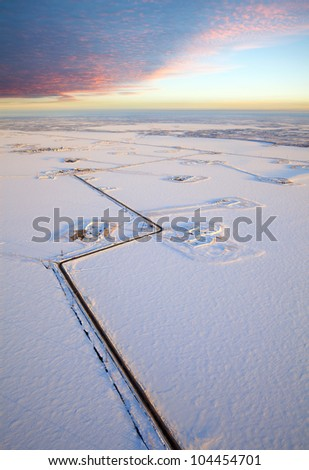 Aerial view of the frozen lake on which are made petroleum production. Roads were run directly through the lake. High clouds bright are lighted by morning sun. - stock photo