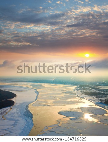 Aerial view of the great river with floating ice floes during sundown. Drifting of ice. Driving of ice. Ice floe. - stock photo