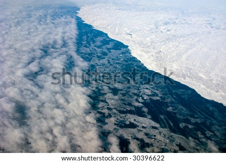Aerial view of the Greenland cloudiness coastline with ocean - stock photo