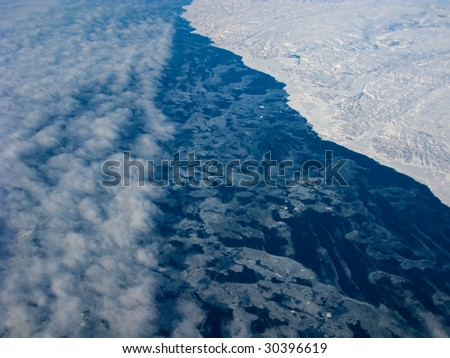 Aerial view of the Greenland coastline and adjacent ocean with clouds - stock photo