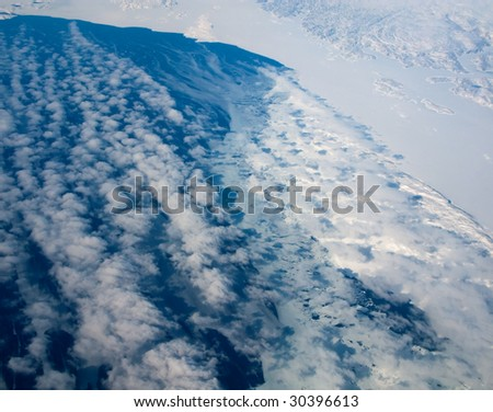 Aerial view of the Greenland coastline with ocean and clouds - stock photo