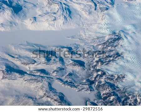 Aerial view of the Greenland with mountain, snow river and waves - stock photo