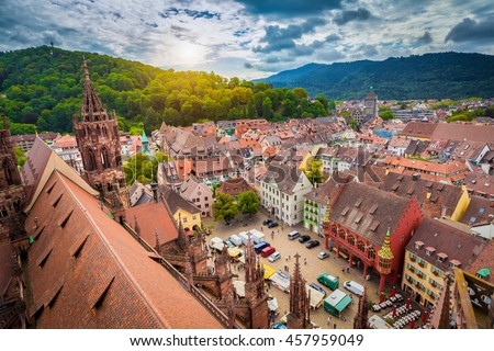 Aerial view of the historic city center of Freiburg im Breisgau from famous old Freiburger Minster in beautiful evening light at sunset with blue sky and clouds in summer, Baden-Wurttemberg, Germany