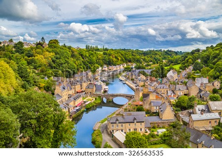 Aerial view of the historic town of Dinan with Rance river with dramatic cloudscape, Cotes-d'Armor department, Bretagne, northwestern France - stock photo