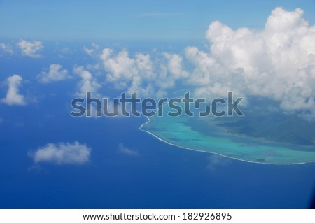 Aerial view of the island of Moorea with clouds, reef and lagoon. Moorea is an island near Tahiti in the tropical archipelago of French Polynesia inside the Pacific ocean.  - stock photo
