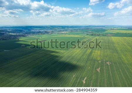 Aerial view of the large green field in spring season - stock photo