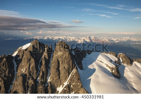 Aerial view of the mountain peak near Squamish, BC, Canada, during a cloudy sunset. - stock photo
