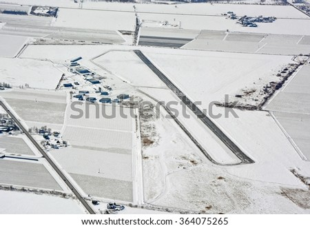 aerial view of the municipal airport of St Catherines, Ontario Canada during Winter, surrounded by snow covered fields  - stock photo