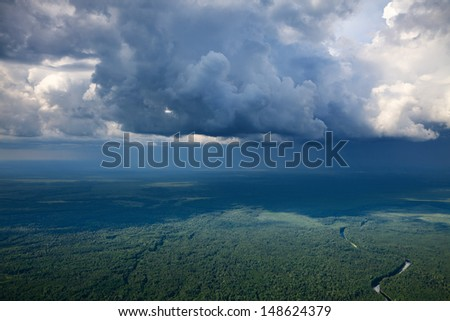 Aerial view of the rain clouds over the forest plain in summer. - stock photo