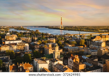 Aerial view of the residential areas of Riga, the Daugava River and the TV tower during sunset. - stock photo