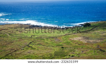 Aerial view of the row of moai statues at Ahu Tongariki with the pacific ocean behind - stock photo