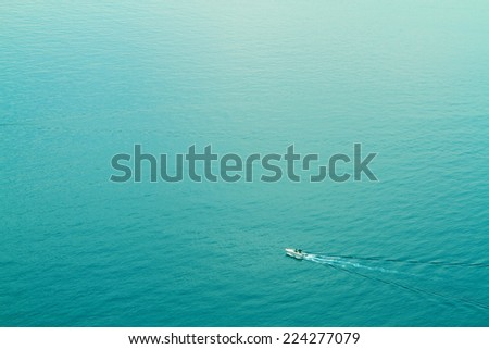 Aerial view of the sea with a motorboat crossing it and leaving white trace - stock photo