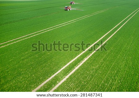 Aerial view of the tractor spraying the chemicals on the large green field - stock photo