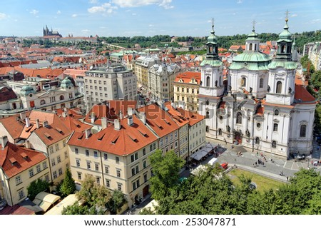 Aerial view of the traditional red roofs of the city of Prague, Czech Republic, with Prague castle in the distance and St. Nicholas church in the Old Town Square. - stock photo
