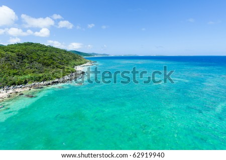 Aerial view of the tropical island, clear blue sea and coral reef on a sunny day, Kume Island, Okinawa, Japan - stock photo