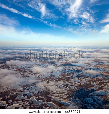 Aerial view of the vast impassable swamps in the autumn. New Snow lies on the bog tussocks. Snow falling from the low clouds - stock photo