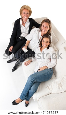 Aerial view of three smiling women of different ages on a white sofa - stock photo
