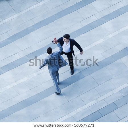 Aerial view of two businessmen giving each other high five on sidewalk - stock photo