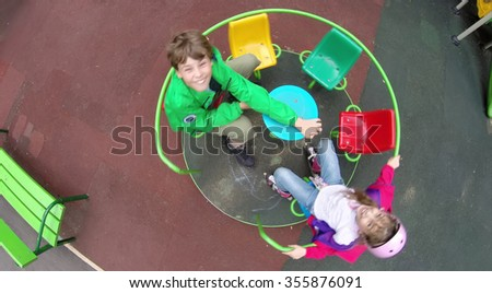 Aerial view of two children are rolling on roundabout.