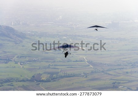 Aerial view of two pilot gliders doing gliding as extreme adrenaline sport - stock photo