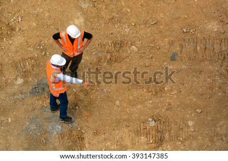Aerial view of two unrecognised civil engineers inspecting construction site. Building development concept with copy space - stock photo