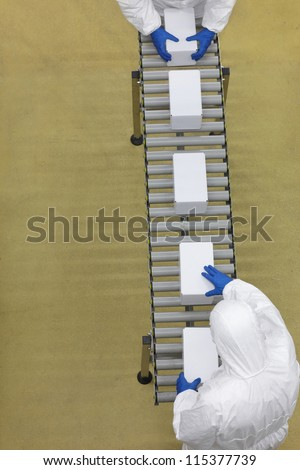 aerial view of two workers in white uniforms working with boxes on packing line - stock photo