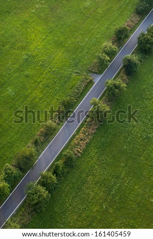aerial view of village  road and  harvest fields  - stock photo