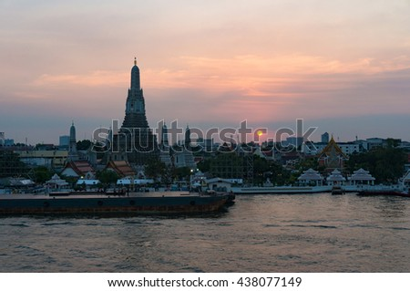 Aerial view of Wat Arun, Temple of Dawn and wharf with sunset sky on the background. Urban Bangkok scene with Buddhist temple - stock photo