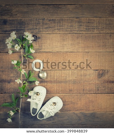 Aerial View of White Vintage Baby Shoes with Antique Teething Ring and White Flower Blossoms on Wood Horizontal Board Background with room or space for copy, text, your words, Vertical instagram tone