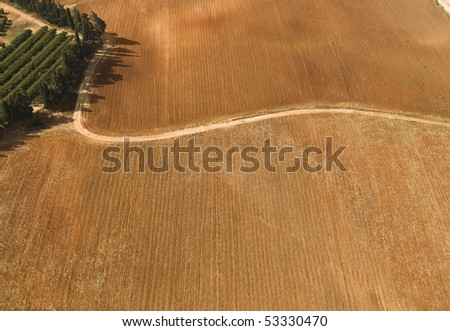 Aerial View of winding Dirt road crossing Plowed Field, in reddish land in the countryside ,Israel - stock photo