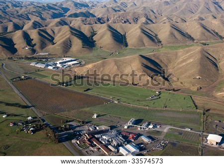 Aerial view of winery and grapevines alongside hills in Blenheim, New Zealand - stock photo