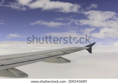Aerial view of wing from jetplane blue sky and big white cloud background