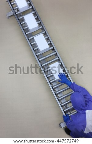 aerial view of worker in blue uniform working with boxes on packing line - stock photo