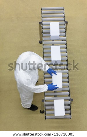 aerial view of  worker in white uniforms working with boxes on packing line - stock photo