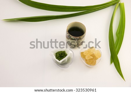 Aerial view on homemade pandan tea bag.  The blended long pandan leaf is stored in small paper tea bag for convenience brewing the hot tea with cane rock sugar for sweet taste. - stock photo