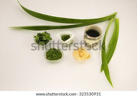 Aerial view on ingredients use for making homemade pandan tea bag.  The blended pandan leaf is stored in small paper tea bag for convenience brewing the hot tea with rock sugar for sweet taste. - stock photo